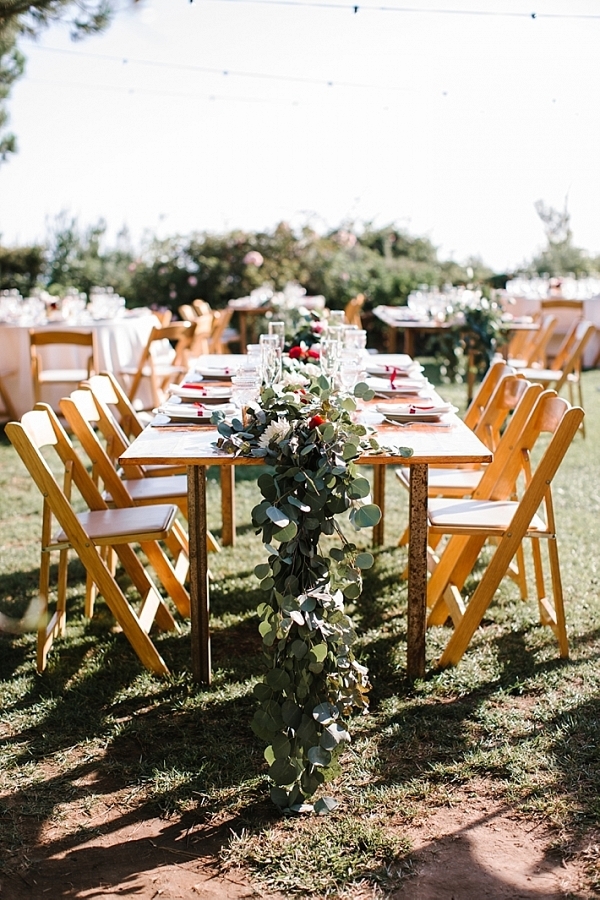 A wooden table with a floral garland