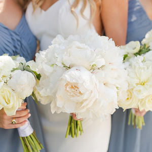 Bridal party in dusty blue gowns and white bouquets