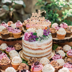 Semi naked wedding cake surrounded by cupcakes
