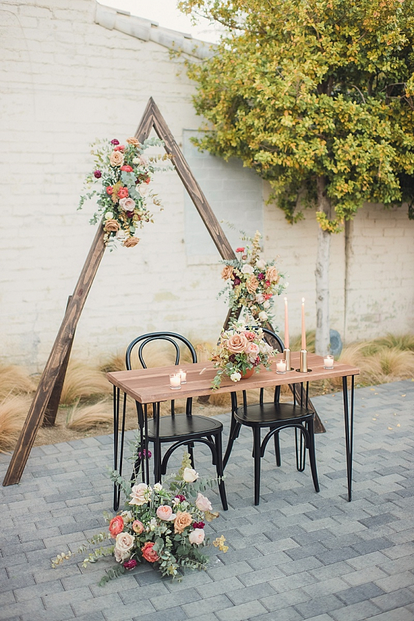 Boho sweetheart table with triangle backdrop
