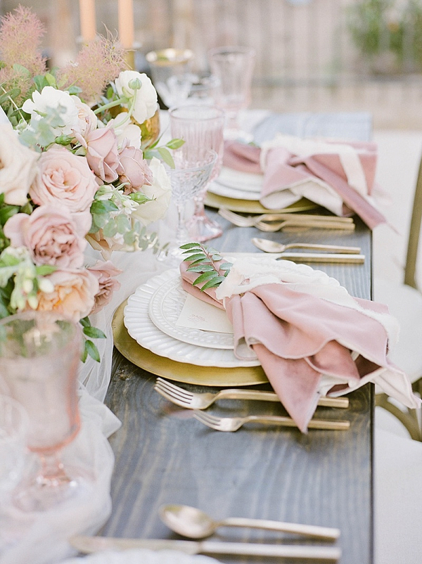 Blush wedding place setting with gold flatware