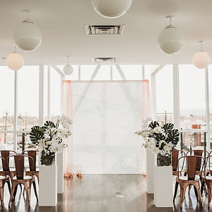 Modern ceremony with draping and copper metal chairs