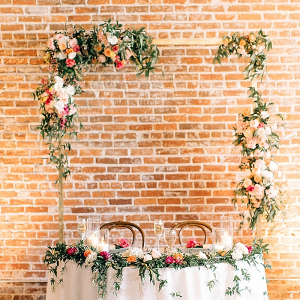 Sweetheart table with floral arch and greenery