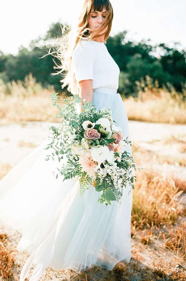 Bride-to-be in blue tulle gown with large organic flowy bouquet.