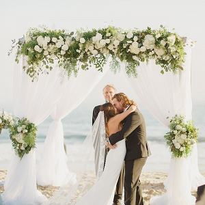 Beach wedding ceremony with draping and floral arch