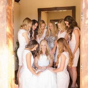 Bridesmaids praying with bride