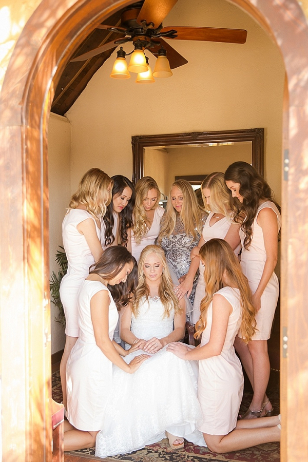 Bridesmaids praying with bride