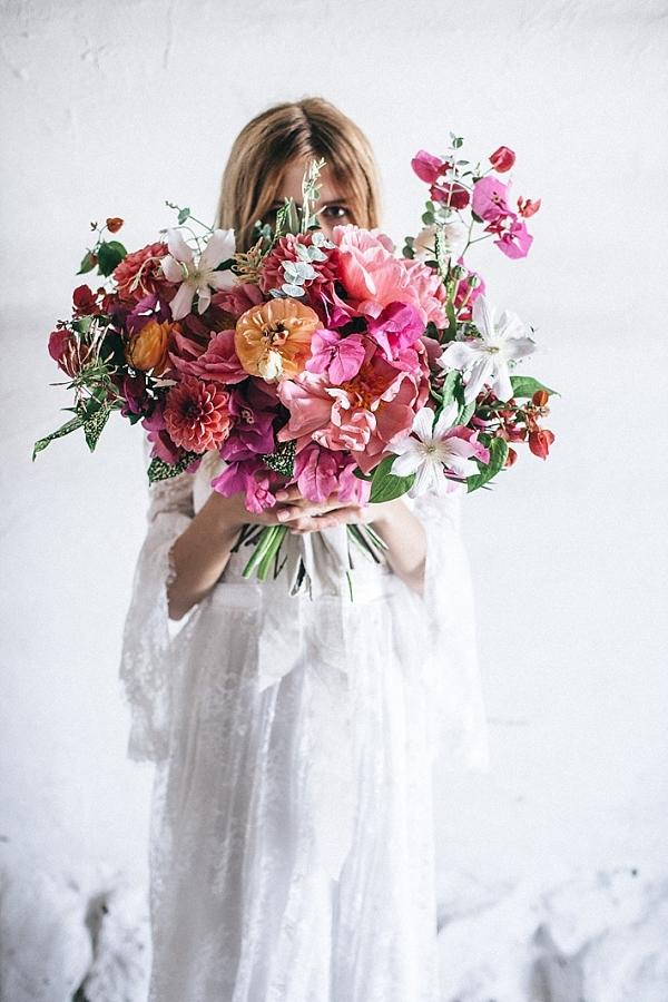 Bride holding large loose pink floral bouquet
