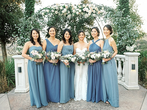 Bridesmaids in mismatched blue dresses