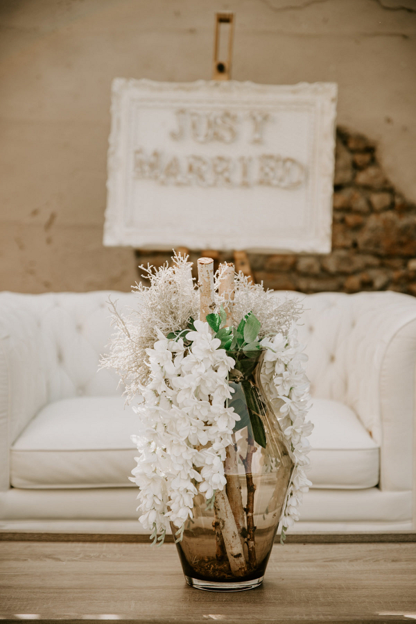 Glass vase with a white couch and a just married sign in the background