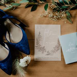 Blue bridal shoes and wedding invitations
