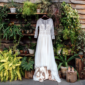 Lace wedding dress surrounded by greenery