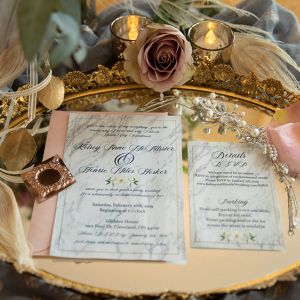 Wedding invitations on a gold tray with an amnesia rose
