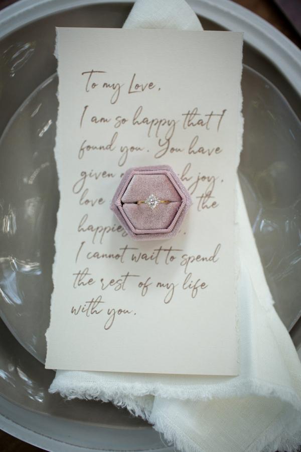 Velvet ring box on top of a handwritten letter