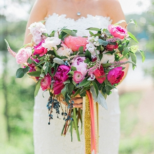 Lush bouquet of blueberry branches and peonies in shades of pink with glittery gold and blush ribbons