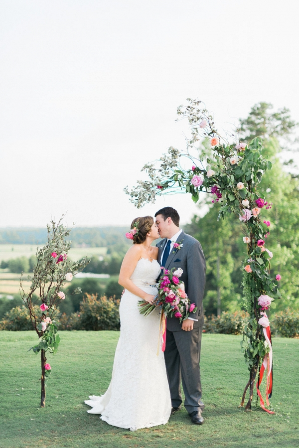 Unclosed, asymmetrical wedding arch with pink peonies and greenery