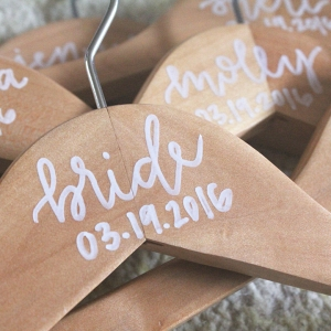 Pretty wedding hangers personalized with painted calligraphy