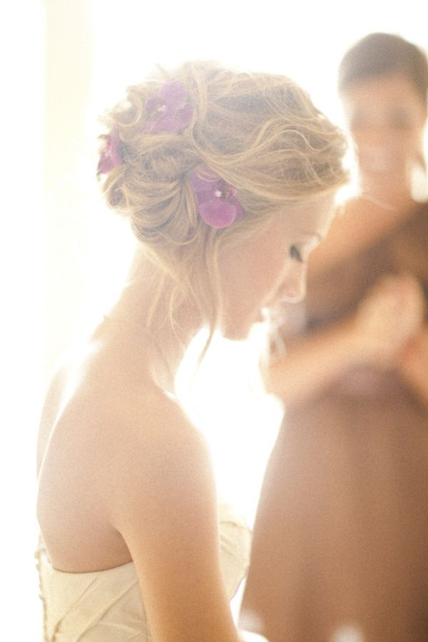 Beautiful bridal hairdo adorned with purple orchids