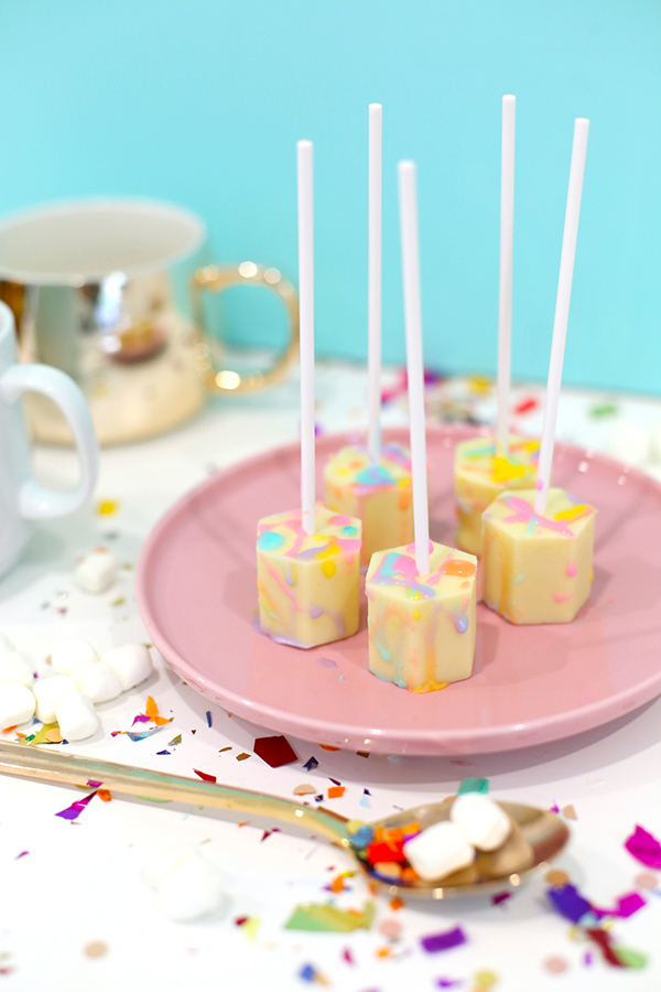 Color-splattered white hot chocolate on a stick