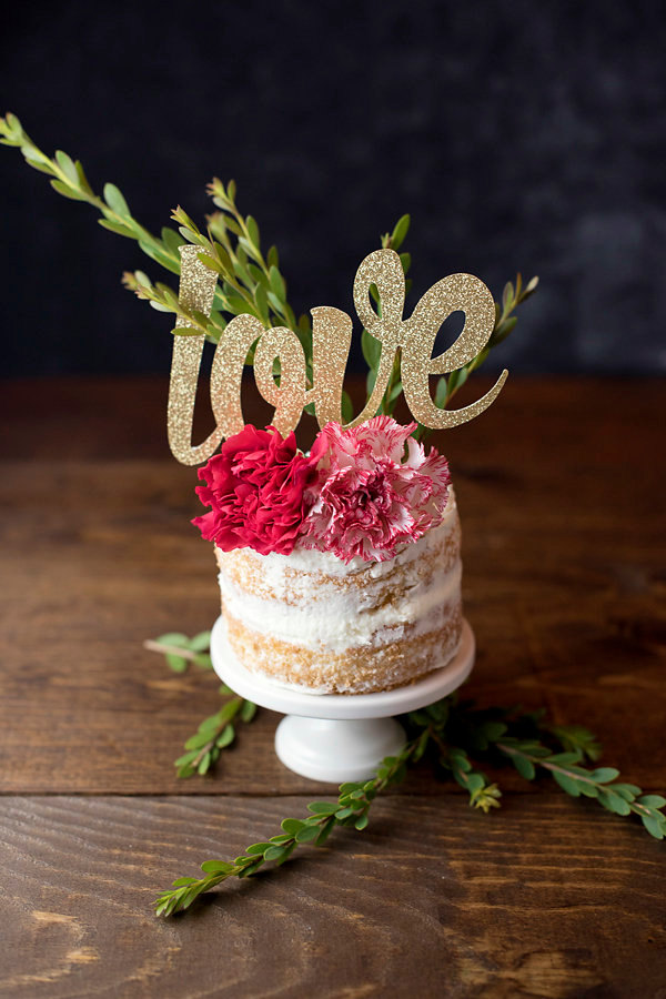 Glittery gold cake topper spelling out the word love