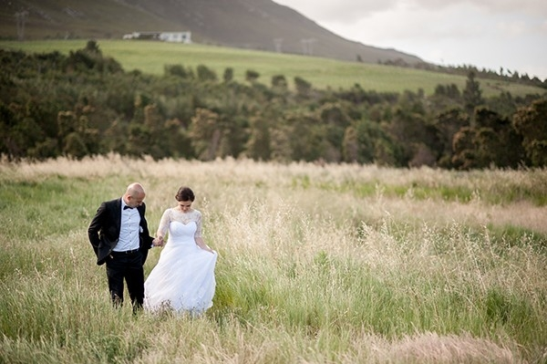 Bride and groom in the fields of Beaumont,  a Bot River family farm and vineyard