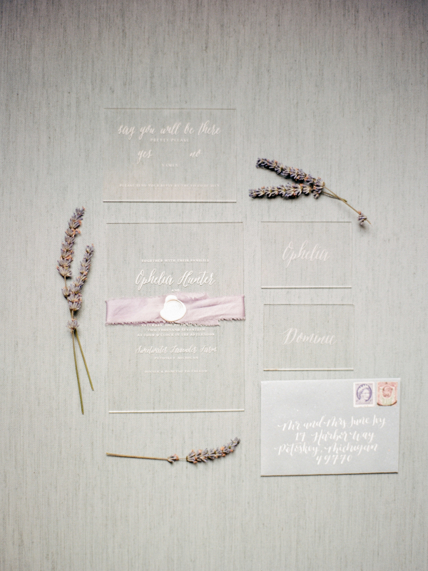 Calligraphed acrylic wedding invitation with a lavender belly band