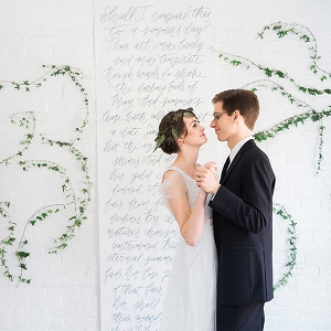 Calligraphed wedding backdrop framed by climbing ivy