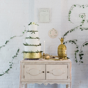 Elegant cake table framed by ivy wall art