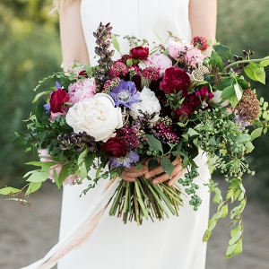 Jewel-toned bouquet with peonies, ranunculi, scabiosas, blueberries, Queen Anne's lace, and lupin