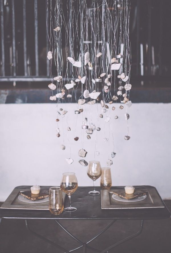 Rock-inspired tablescape with an earthy chandelier made out of stones and tea lights