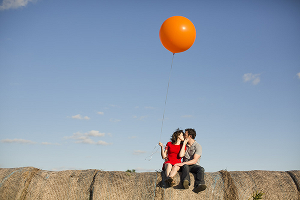 Couple sitting atop a hay bale and holding a giant red balloon