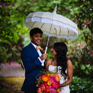 Indian bride and groom under umbrella