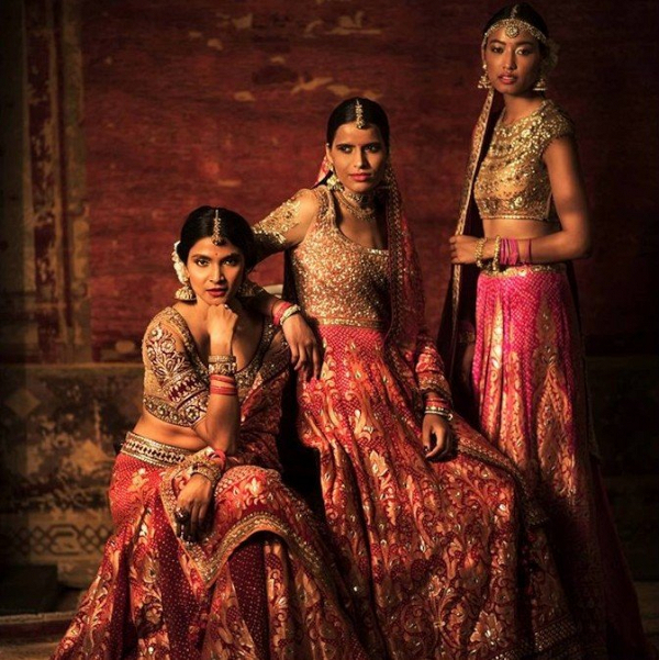 Pink, red, and gold saris