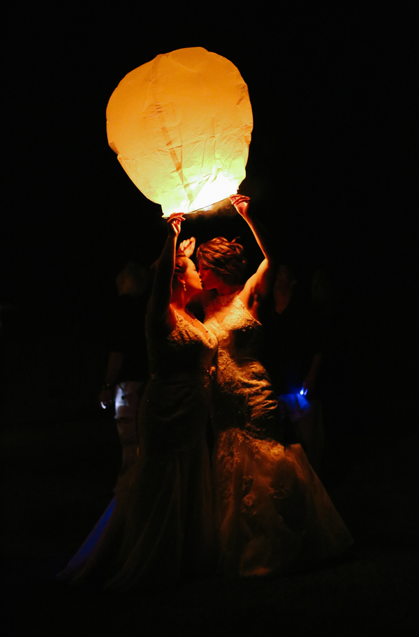 Two brides releasing chinese lanterns at a wedding