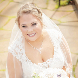 Bride in lace wedding dress with white and blush bouquet