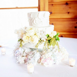Small buttercream wedding cake with fresh flowers