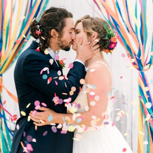 Colorful wedding ceremony with streamer backdrop