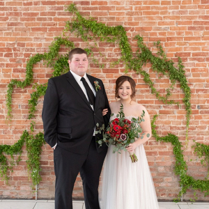 Bride and groom with greenery wedding ceremony backdrop