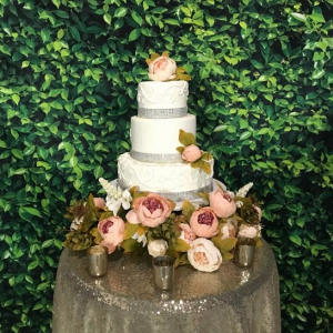 Wedding cake with faux boxwood backdrop