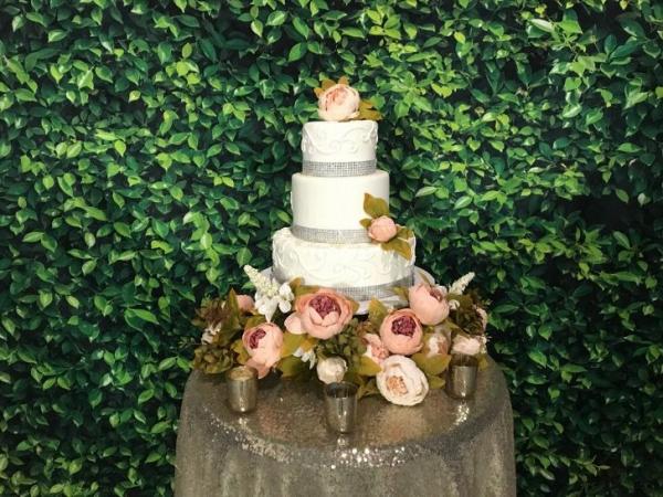 Wedding cake with faux boxwood backdrop
