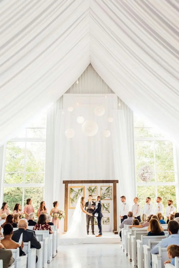 Open white barn wedding ceremony