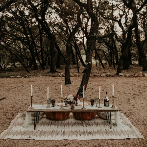 Boho wedding table in forest with pillows on rug