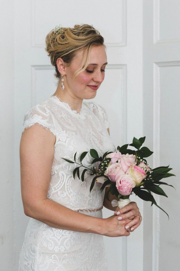 Bride in lace gown with classic pink rose bouquet