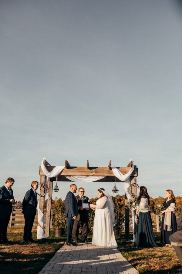 Outdoor wedding ceremony under arbor