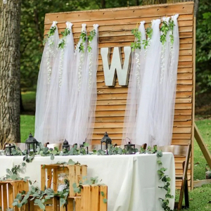 Rustic sweetheart table with wooden backdrop