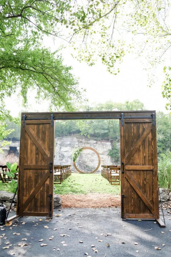 Outdoor ceremony with circle arch and barn door entrance