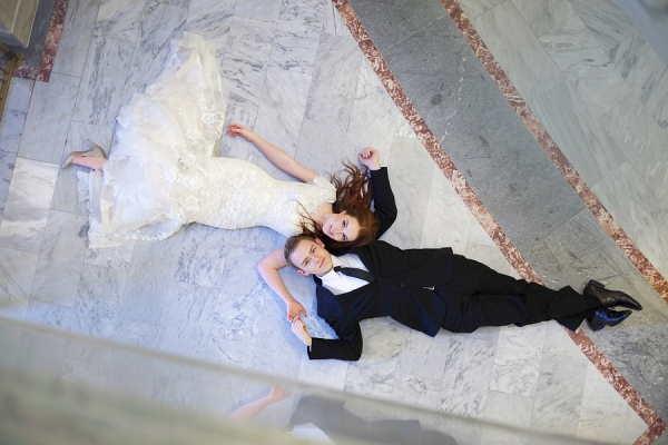 Bride and groom lying on a marble floor
