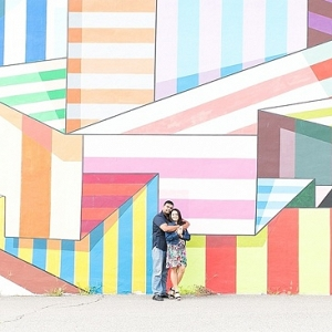 Couple in front of colorful wall mural