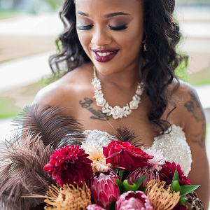 Glamorous Black Bride with Tattoos and Feather Bouquet