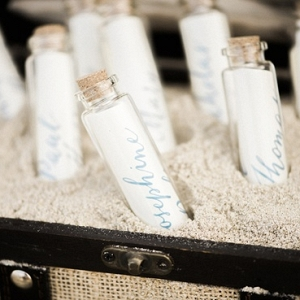 Place cards in tiny glass bottles